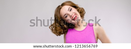 Charming young girl in pink dress on gray background. Young girl pulls her hand out #1213656769