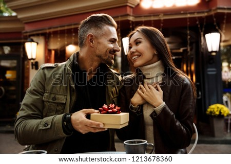 Couple. Holiday. Cafe. Man is giving a gift box to his woman. Both are in warm casual clothes smiling while sitting in the cafe outdoors #1213678360