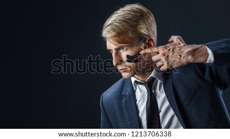 Businessman with war paint on his face. Risk management concept. young guy in suit with tie is preparing for a difficult job, make a war paint on the face Royalty-Free Stock Photo #1213706338