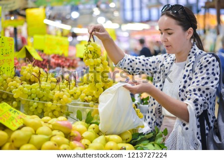 woman is selecting fruits in cotton bag at local food market. zero waste shopping concept #1213727224