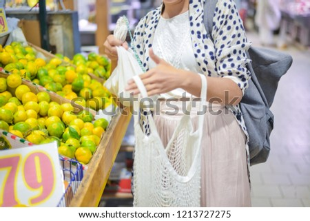 woman is selecting fruits in cotton bag at local food market. zero waste shopping concept #1213727275