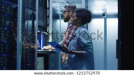 Modern multiethnic man and woman with tablet using laptop in server room while checking servers #1213752970