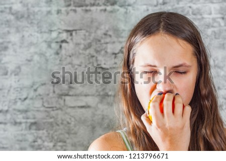 portrait of young teenager brunette girl with long hair eating persimmon kaki fruit on gray wall background #1213796671