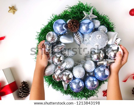 Put the silver ball into a Christmas wreath placed on a white table #1213843198