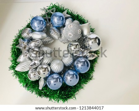 A Christmas wreath with silver decorating balls placed on a white background #1213844017