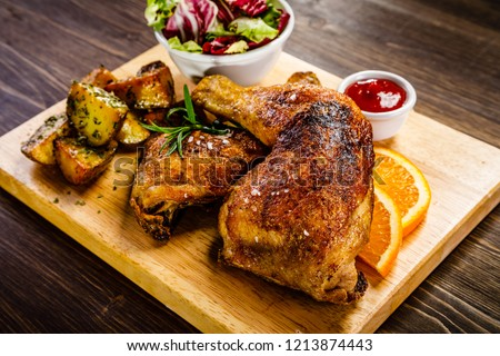 Grilled chicken legs with baked potatoes and vegetable salad on wooden table #1213874443