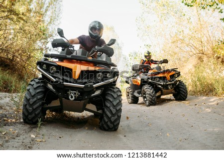 Two quad bike riders travels in forest, front view #1213881442