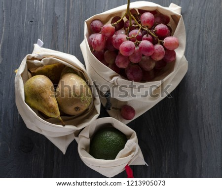 pink round grapes avocado pears in a linen bag