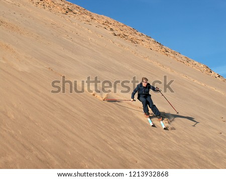 Beautiful girl Sand skiing down dunes in desert. Sand-skiing is sport and form of skiing in which skier rides down sand dune on skis, using ski poles, as done with other types of skiing. #1213932868
