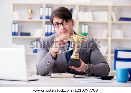 Businessman with golden cup in the office #1213999708