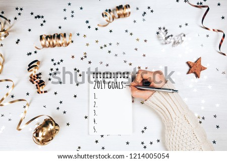 Wish lift for New Year. Holiday decorations and notebook with wish list on white rustic table, flat lay style. Planning concept. #1214005054