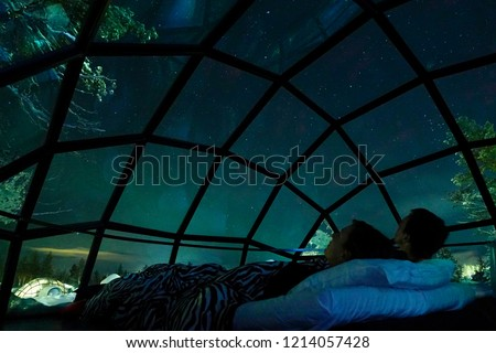 CLOSE UP Young Caucasian tourist couple observing the night sky from a cool glass house in the Scandinavian wilderness. Girlfriend and boyfriend enjoying a romantic evening in a cool glassy igloo. #1214057428