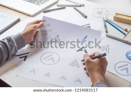 Graphic designer drawing sketch design creative Ideas draft Logo product trademark label brand artwork. Graphic designer studio Concept. #1214083117