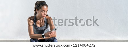 Fitness runner girl listening to music with earphones on phone wearing smartwatch. Active lifestyle woman wearable tech sports gear concept banner panorama. Royalty-Free Stock Photo #1214084272