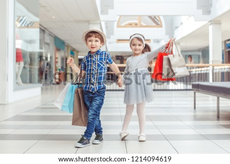 Group portrait of two cute adorable preschool children going shopping. Caucasian little girl and boy running in mall. Kids holding shopping bags. Black Friday sale concept.  #1214094619
