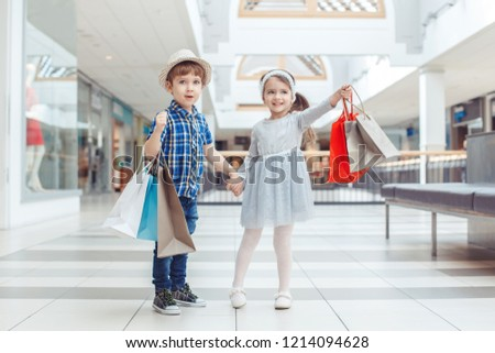Group portrait of two cute adorable preschool children going shopping. Caucasian little girl and boy running in mall. Kids holding shopping bags. Black Friday sale concept.  #1214094628