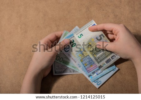Hand holding American dollar  banknotes isolated on wooden background #1214125015