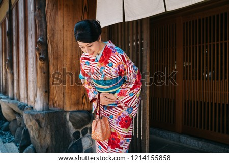 Japanese lady bowing in front of her house with beautiful kimono. traditional lifestyle in jp. attractive woman with colorful kimono clothing in summer. Royalty-Free Stock Photo #1214155858