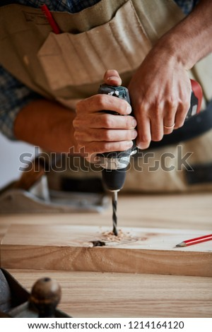 Carpenter drills a hole with an electrical drill, Wood boring drill in hand drilling hole in wooden block #1214164120
