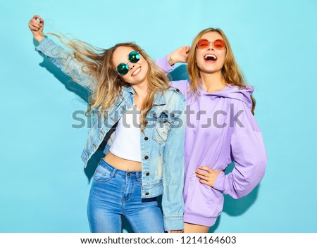 Two young beautiful blond smiling hipster girls in trendy summer clothes. Sexy carefree women posing near blue wall in sunglasses. Positive models going crazy #1214164603