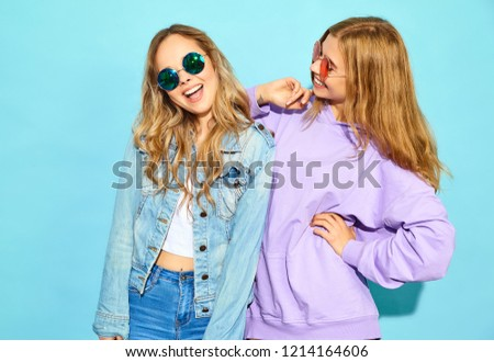 Two young beautiful blond smiling hipster girls in trendy summer clothes. Sexy carefree women posing near blue wall in sunglasses. Positive models going crazy #1214164606