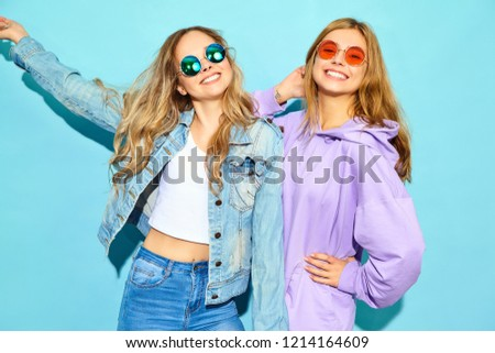Two young beautiful blond smiling hipster girls in trendy summer clothes. Sexy carefree women posing near blue wall in sunglasses. Positive models going crazy #1214164609