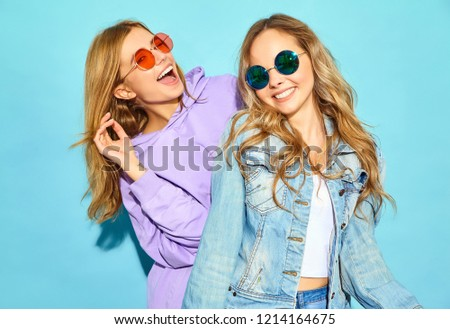Two young beautiful blond smiling hipster girls in trendy summer clothes. Sexy carefree women posing near blue wall in sunglasses. Positive models going crazy and hugging #1214164675