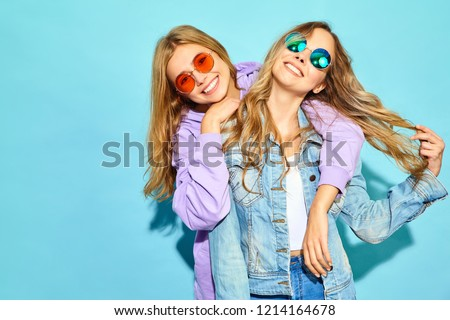 Two young beautiful blond smiling hipster girls in trendy summer clothes. Sexy carefree women posing near blue wall in sunglasses. Positive models going crazy and hugging #1214164678