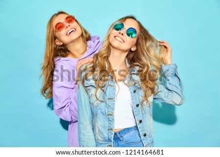 Two young beautiful blond smiling girls in trendy summer clothes.  #1214164681