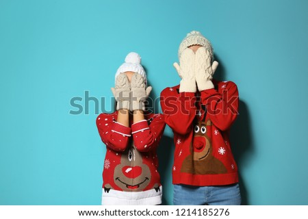 Young couple in Christmas sweaters and knitted hats on color background #1214185276