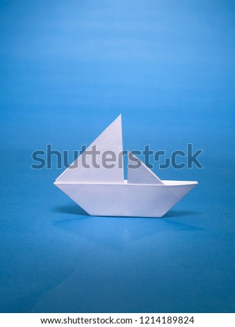 A STILL LIFE OF A PAPER SAIL BOAT MADE WITH THE ART OF ORIGAMI