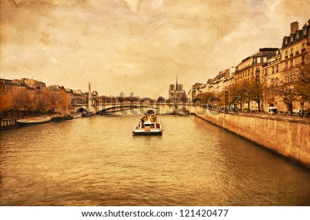 vintage textured picture of the river Seine in Paris with a tourist boat and the Notre Dame Cathedral in the background
