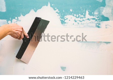 Hand with putty knife repair wall, Hand with a spatula, spatula with spackle paste structure, process of applying layer of putty trowel, working with spackling paste #1214229463
