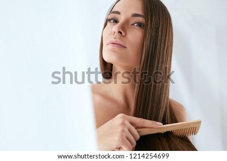 Beauty Hair Care. Beautiful Woman Combing Long Natural Hair Royalty-Free Stock Photo #1214254699
