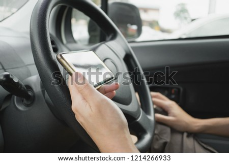 blur man hand holding mobile phone inside car  #1214266933