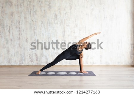 Young attractive woman practicing yoga and stretching body against concrete wall Girl standing in Utthita parsvakonasana exercise, Extended Side Angle pose, wearing black sportswear, yoga studio #1214277163