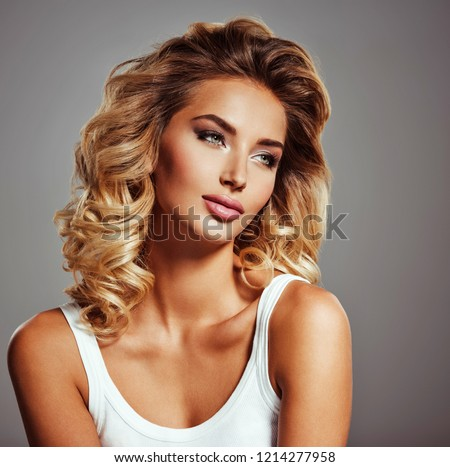 Photo of a beautiful young blond girl with curly hair. Closeup attractive sensual face of white woman with long hair. Smokey eye makeup. #1214277958