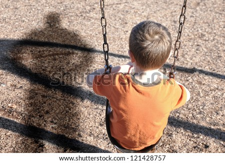 A young boy is sitting on a swing set and looking at a shadow figure of a man or bully at a playground. Use it for a kidnap, defense or safety concept. #121428757