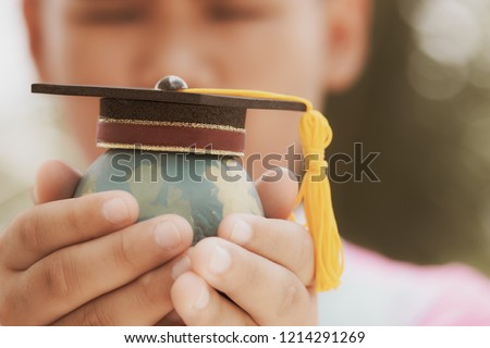 Education in Global, Graduation cap on top model Earth in student hands. Concept of abroad international Educational and save world. Back to School and Studies lead to success in world wide. Royalty-Free Stock Photo #1214291269