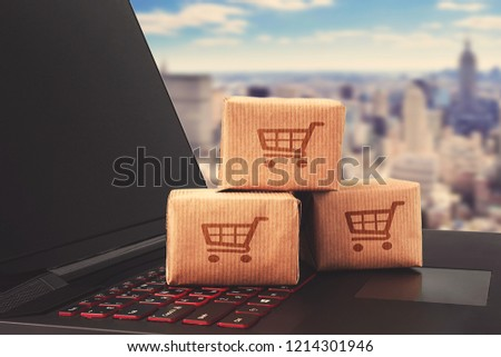 Online shopping / ecommerce and delivery service concept : Paper cartons with a shopping cart or trolley logo on a laptop keyboard, depicts customers order things from retailer sites via the internet. #1214301946