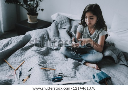 Nice Girl Listens Music in Headphones in Bedroom. Frowning Little Black-Haired Child Holds Smartphone Sits on Large Gray Bed in Modern Apartment Uses White Earphones. Leisure Time Concept #1214461378