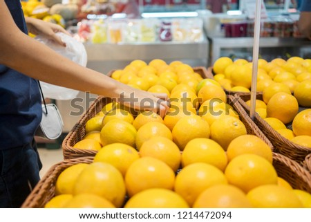 Closeup of young woman hand pick up orange fruit on the boxes in the supermarket #1214472094