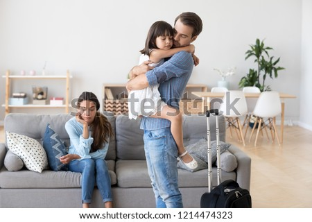 Unhappy diverse family in living room at home. Sad father hugs hold on hand small daughter, mother sitting on sofa. Parents divorcing, child stay with mommy dad leave with suitcase. Break up concept #1214474323