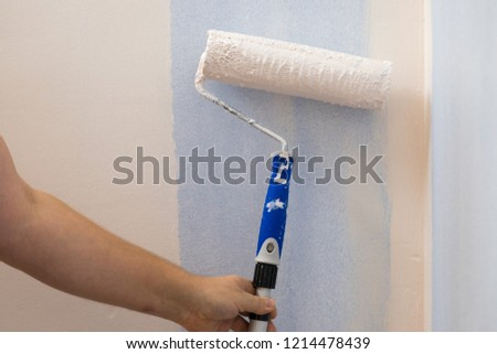 Person appplying paint on wall using roller brush. Home renovation concept. #1214478439