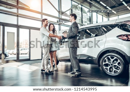 Young couple shaking hands with sales agent after a successful car buying. Royalty-Free Stock Photo #1214543995