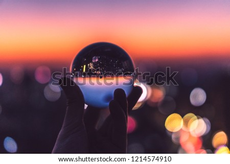 Crystal glass ball during sunset on a cityscape with bokeh