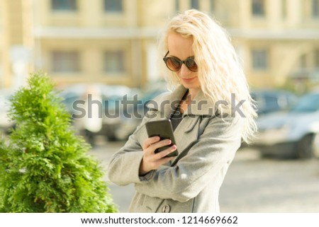 Adult smiling blonde woman talking on cell phone, city street background, autumn sunny day, golden hour #1214669662