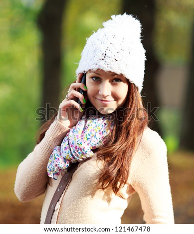 Pretty young woman talking on new cell phone in park #121467478