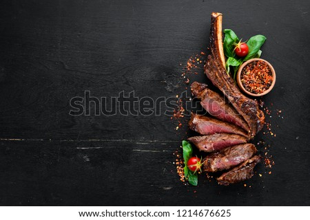 Steak on the bone. tomahawk steak On a black wooden background. Top view. Free copy space. #1214676625