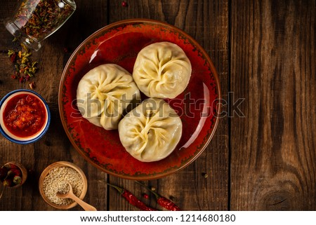 Traditional manti food on plate with sauce, top view #1214680180